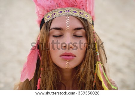 Beauty portrait of the girl with flash tattoo and coloured feather hat - stock photo