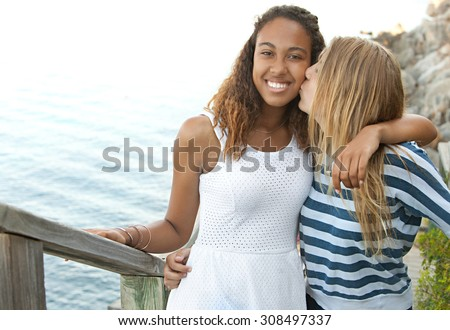 Beauty portrait of two teenager girls of different ethnic origins friends hugging and kissing, smiling by a spacious blue sea on a summer holiday, outdoors. Travel lifestyle, nature beach exterior.