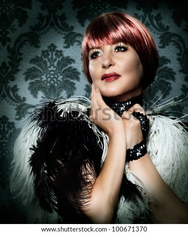 beauty portrait of woman in Marlene Dietrich stile with feather boa - stock photo