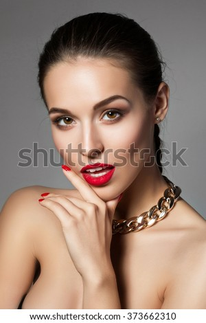 Beauty portrait of young aristocratic woman with red lips and nails touching her face. Classic evening make up. Brown smokey eyes - stock photo