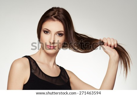 Beauty portrait of young attractive brunette touching her healthy shiny hair. Fashion Caucasian woman with long straight brown hair posing in studio.  - stock photo