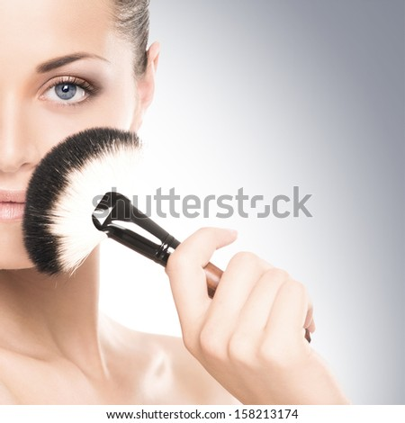 Beauty portrait of young, attractive, fresh, healthy and natural woman with the makeup brush isolated on white - stock photo
