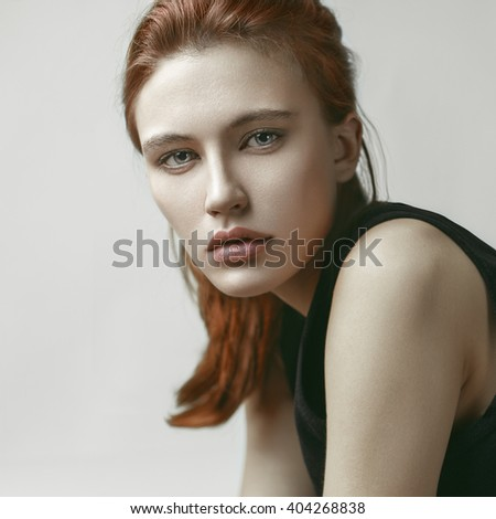 Beauty portrait of young beautiful red-haired model with long straight hair. Makeup. Skin care. - stock photo