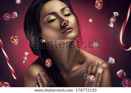 Beauty portrait of young beautiful woman with candy around her - stock photo