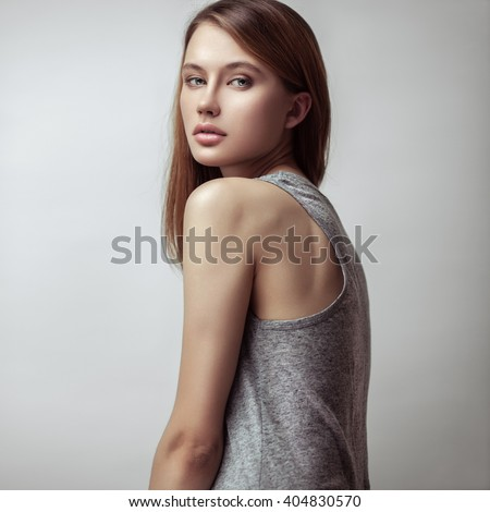Beauty portrait of young pretty red-haired girl with long straight hair. Professional nude makeup. Vogue style. Posing in studio. - stock photo