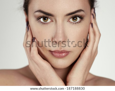 Beauty portrait of young pretty woman with perfect clean skin touching her face. Attractive Caucasian brunette model posing in studio.  - stock photo
