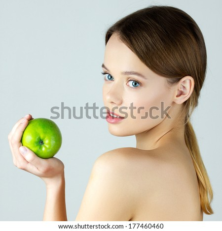 Beauty portrait of young woman holding green apple. Healthy lifestyle concept - stock photo