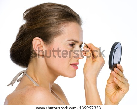 Beauty portrait of young woman looking into mirror and using tweezers