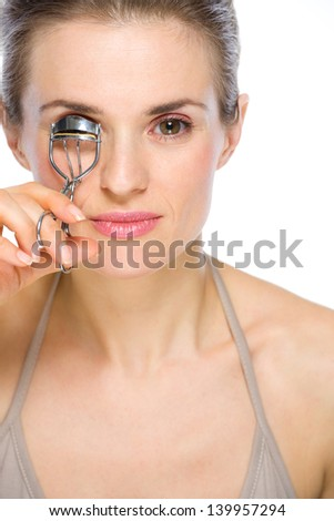 Beauty portrait of young woman using eyelash curler - stock photo