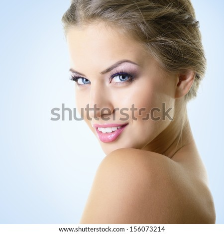 Beauty portrait of young woman with beautiful healthy face with nice makeup looking at camera, studio shot of attractive girl over blue background - stock photo