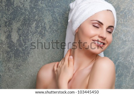 Beauty portrait of young woman with towel on head at spa