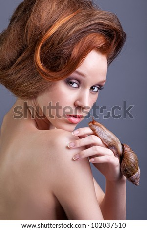 Beauty portrait on young stylish woman with creative hairstyle and with snail - stock photo