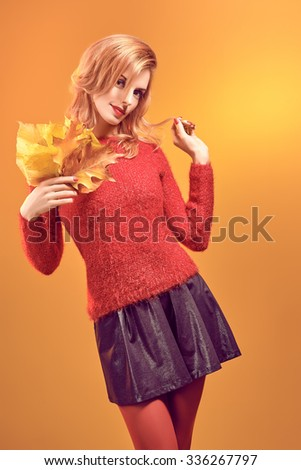 Beauty portrait redhead young model woman, autumn leafs in hands. Attractive happy playful girl in stylish red sweater, people. Retro, vintage, creative toned.Orange yellow background, copy space