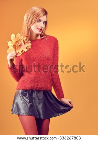 Beauty portrait redhead young model woman, autumn leafs in hands. Attractive happy playful girl in stylish red sweater smiling, people.Retro, vintage, creative toned.Orange yellow background, copy space