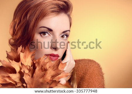 Beauty portrait redhead young woman with autumn leafs in hands. Attractive happy girl dreams, romantic. People face closeup, makeup. Retro, vintage, creative toned, orange yellow background, copyspace - stock photo