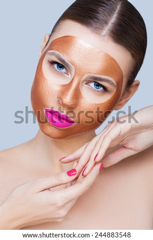 Beauty portrait with a gold peel-off mask