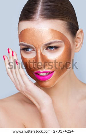 Beauty portrait with a gold peel-off mask - stock photo