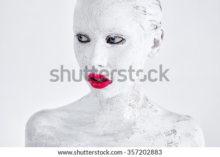 Beauty portrait with creative make-up, painted white textured face paint and bright red lips and blue eyes on a white background
