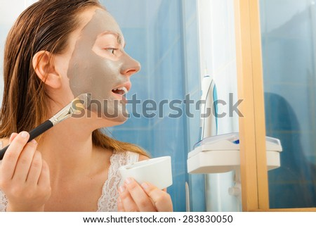 Beauty procedures skin care concept. Young woman applying facial gray mud clay mask to her face in bathroom - stock photo