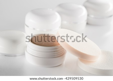 Beauty product of beige color for hiding all the defects of the skin. Qualitative concealer with the sponge on its jar. Objects in the foreground. The gradation of the tan.