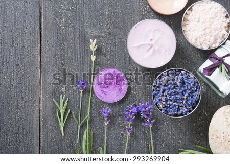 beauty product samples with fresh purple and blue dried lavenders, bath salts on dark wood table background - stock photo