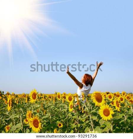 beauty redhaired woman in sunflower field - stock photo