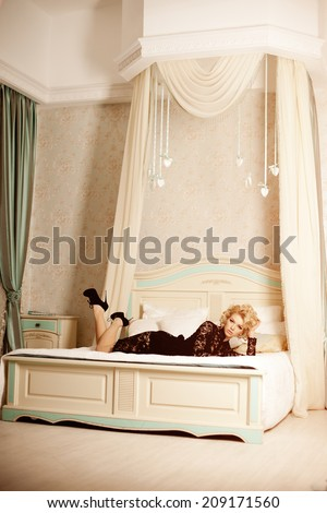 Beauty rich luxury woman like Marilyn Monroe. Beautiful fashionable girl in  retro interior in the bedroom on the bed  - stock photo