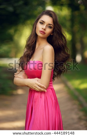 Beauty romantic girl outdoor. Pretty young model dressed in long evening dress posing outdoors at path in the park. Full body Portrait with beautiful bokeh - stock photo