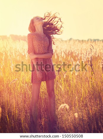 Beauty Romantic Girl Outdoors. Beautiful Teenage Model girl Dressed in Casual Short Dress on the Field in Sun Light. Blowing Long Hair. Autumn. Glow Sun, Sunshine. Backlit. Toned in warm colors  - stock photo