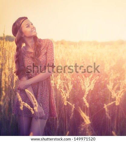 Beauty Romantic Girl Outdoors. Beautiful Teenage Model girl Dressed in Fashionable Short Dress Posing on the Field in Sun Light. Glow Sun. Autumn. Toned in warm colors. Copy Space for your text - stock photo