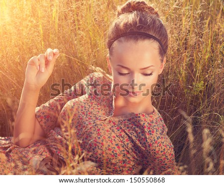 Beauty Romantic Girl Outdoors. Beautiful Teenage Model girl Lying on the Field in Sun Light. Autumn. Glow Sun, Sunshine. Backlit. Toned in warm colors  - stock photo