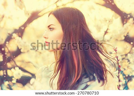Beauty Romantic Girl Outdoors enjoying nature. Beautiful Model girl with long healthy blowing hair in Spring garden, Sun Light. Glow Sun. Free Happy Woman. Toned in warm colors