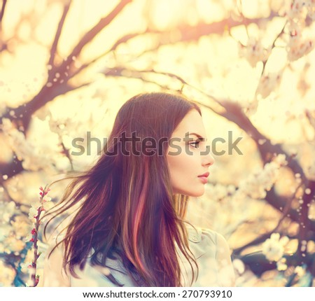 Beauty Romantic Girl Outdoors enjoying nature. Beautiful Model girl with long healthy blowing hair in Spring garden, Sun Light. Glow Sun. Free Happy Woman. Toned in warm colors - stock photo