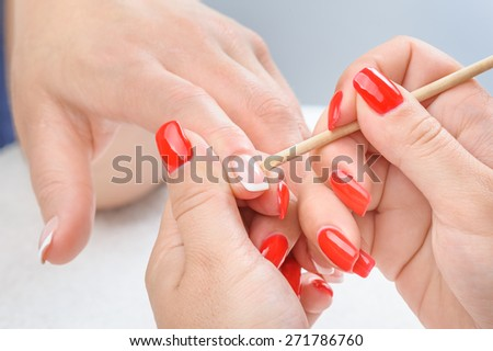 beauty salon, manicure applying, cleaning the cuticles with wooden stick