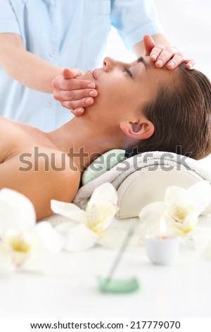 Beauty salon, the woman at face massage .Masseuse - woman at face massage .Attractive brunette woman in spa salon  - stock photo