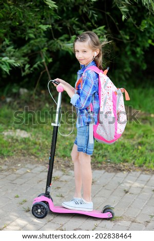 Beauty school age  kid girl in plaid shirt and jeans skirt with rucksack rides on her pink scooter from the school and listen to the music with her cell phone - stock photo