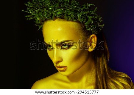 Beauty serious sexy woman with makeup and wreath on head in studio