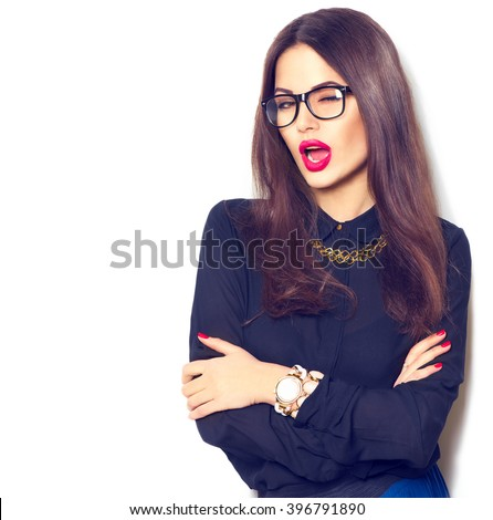 Beauty sexy winking fashion model girl wearing glasses, isolated on white background. Beautiful young brunette woman with trendy accessories posing in studio - stock photo