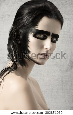 beauty shoot of pretty young girl with strong black painted make-up on her visage and on hair. Looking in camera with charming eyes  - stock photo
