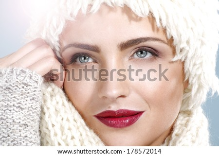 beauty shot of a beautiful woman in winter clothes on blue - stock photo