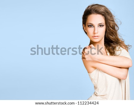 Beauty shot of a young brunette beauty on wide blue banner. - stock photo