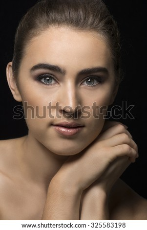 Beauty shot of brunette woman with smoky eyes on black background