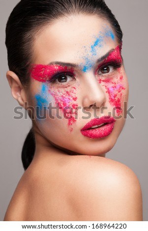 Beauty shot of fashionable womans face with pink, red and blue dry powders. red glitters on lips. FaceArt - stock photo