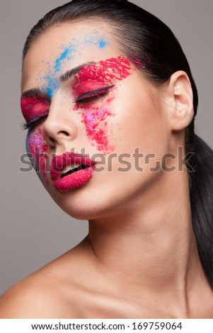 Beauty shot of fashionable women face with pink, red and blue dry colours. red glitters on lips. FaceArt - stock photo