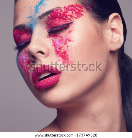 Beauty shot of fashionable women face with pink, red and blue dry colours. red glitters on lips. Square - stock photo