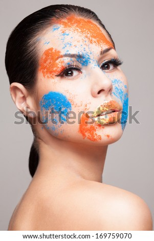 Beauty shot of woman`s face with orange and blue dry powders. gold glitters on lips. FaceArt - stock photo