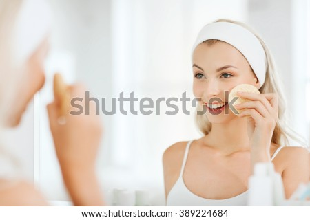 beauty, skin care and people concept - smiling young woman washing her face with facial cleansing sponge at bathroom - stock photo