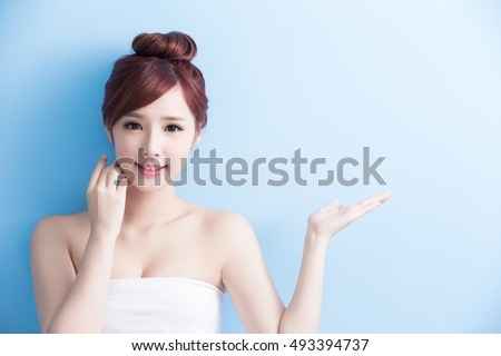 Beauty  skin care woman with charming smile and show something to you with health skin and hair isolated on blue background, asian beauty