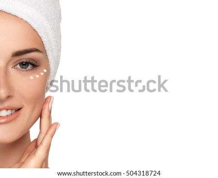 Beauty smiling Girl with towel on head applies cream on face, isolated on white. Concept of healthcare, beauty and youth. Close up photo of Beautiful woman with hand near face. Drops cream around eyes