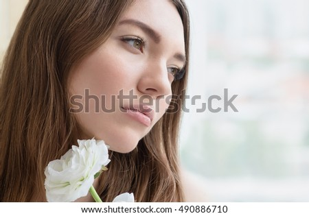Beauty smiling model with natural make up, long eyelashes and flower. Youth and  skin care concept. Spa and wellness. Make up, long hair and lashes. Close up, selective focus.